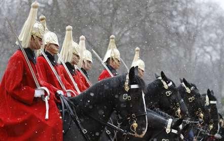 Membros da cavalaria no desfile da Guarda de Cavalos debaixo de queda de neve, em Londres (Frank Augstein/AP)