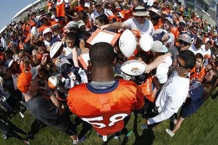 Von Miller, dos Denver Broncos, assina autógrafos no arranque da pré-época da NFL. (Foto David Zalubowski/AP)