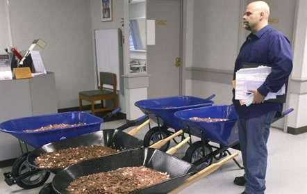 Em sinal de protesto devido a uma coima com que foi sancionado, Nick Stafford, pagou em cêntimos, apresentando-se na repartição de finanças com cinco carrinhos-de-mão cheios de moedas, na Virgínia (David Criggeru/AP)