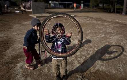 Crianças refugiadas sírias brincam com rodas no campo de refugiados de Ritsona, a cerca de 100 quilómetros a norte de Atenas. Mais de 62 mil refugiados e migrantes estão presos na Grécia depois de uma série de encerramentos nas fronteiras com os Balcãs (Muhammed Muheisen/AP)