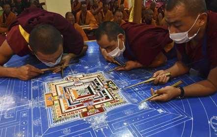 Monges budistas preparam uma Mandala de areia, símbolo espiritual e ritual que representa o universo budista, durante o quarto dia de Kalachakra, em Bodhgaya (Manish Bhandari/AP)
