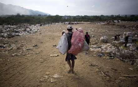 Um homem carrega sacos de material reciclável que apanhou num depósito de lixo em Puerto Cabello, cidade portuária onde chega a maior parte da comida importada do país (Ariana Cubillos/AP)